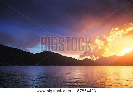 Red vivid clouds illuminated by the beam of the sun and dark ominous sky. Wonderful natural background. Phenomenon of nature. Picturesque and gorgeous morning scene. Discover the world of beauty.