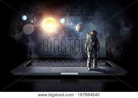 Space explorer and laptop. Mixed media