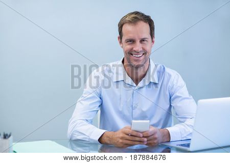 Portrait of smiling doctor using mobile phone in dental clinic