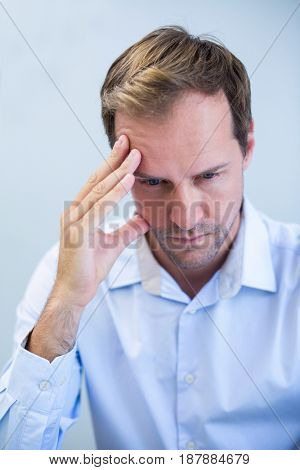 Close-up of tensed dentist sitting with hand on forehead in clinic