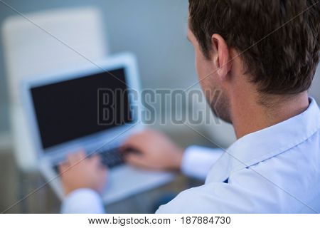Dentist working on laptop in dental clinic
