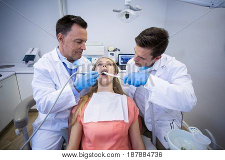 Dentists examining a female patient with tools in clinic