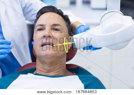 Dentist examining a male patient with tool in clinic