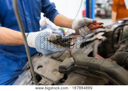 car service, repair, maintenance and people concept - auto mechanic man with cleats charging battery at workshop