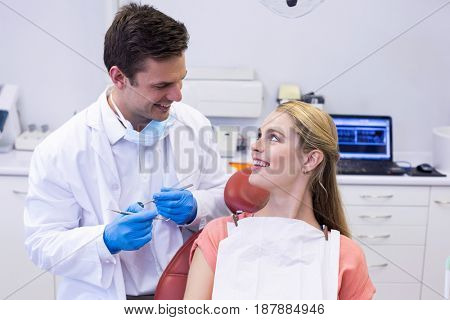 Dentist interacting with female patient while examining in clinic