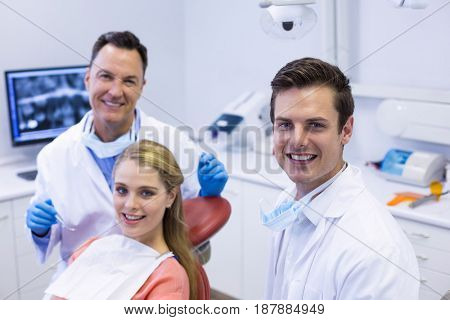 Portrait of smiling dentists and female patient in clinic