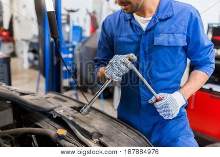 car service, repair, maintenance and people concept - auto mechanic man with wrench and lamp working at workshop