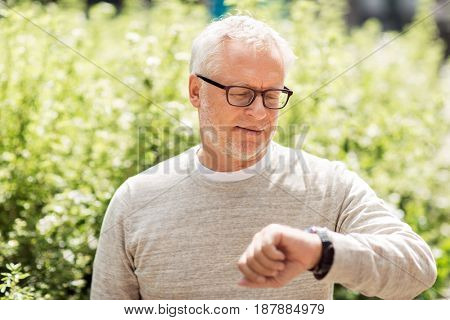 punctuality and people concept - senior man checking time on wristwatch or smart watch on his hand outdoors