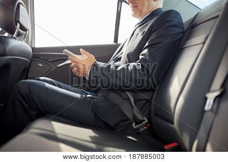 transport, business trip, technology and people concept - senior businessman texting on smartphone and driving on car back seat
