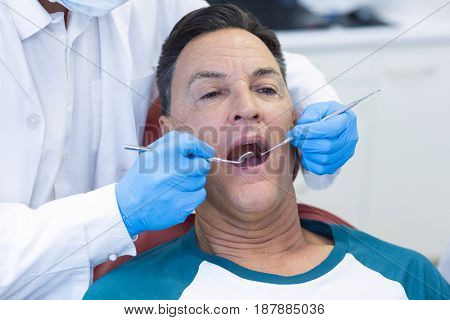 Dentist examining a male patient with tools in clinic