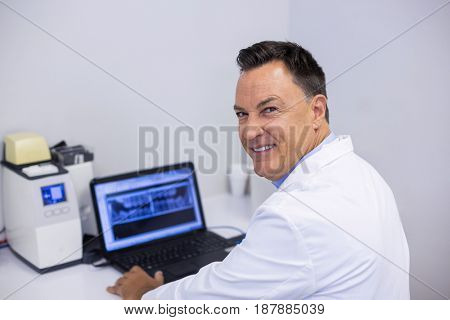 Portrait of happy dentist examining x-ray report on laptop in clinic