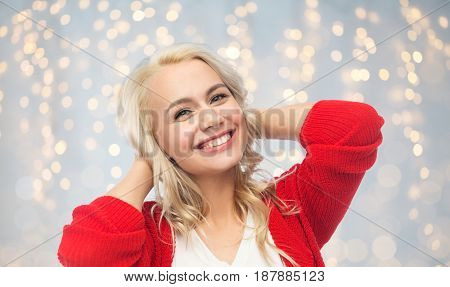 fashion, portrait and people concept - happy smiling young woman in red cardigan over holidays lights background