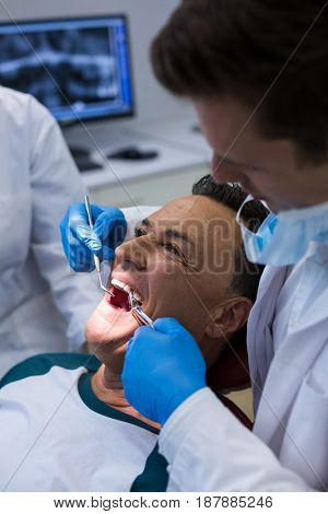 Dentists examining a male patient with tools in clinic