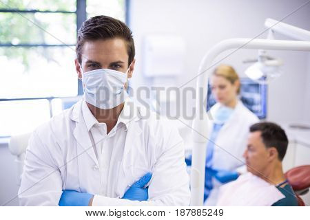 Portrait of dentist wearing surgical mask while his colleague examining patient in background