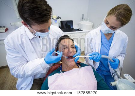 Dentists giving anesthesia to male patient in clinic