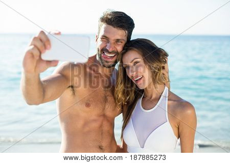 Close-up of happy young couple taking selfie at beach