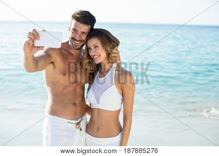 Happy young couple taking selfie while standing on shore at beach