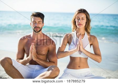 Young couple meditating while sitting on shore at beach