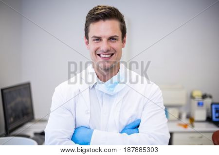 Portrait of happy dentist standing with arms crossed in clinic