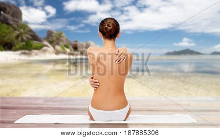 beauty, people and bodycare concept - beautiful topless young woman in white panties sitting on towel from back over exotic beach background