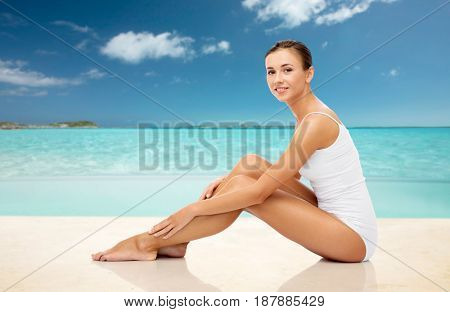 beauty, people and bodycare concept - beautiful woman in white underwear touching her smooth bare legs over exotic tropical beach background
