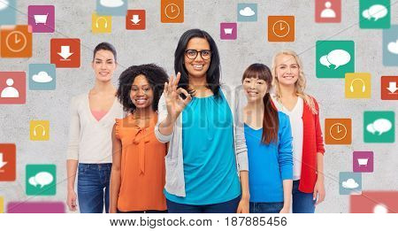 diversity, multimedia and people concept - international group of happy smiling different women showing ok hand sign over gray background with media icons