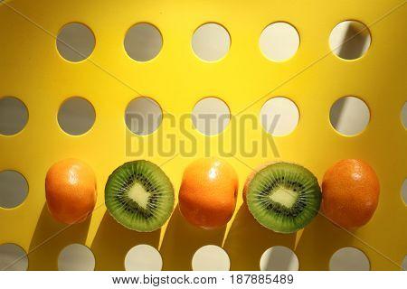 Fresh tangerines and halves of kiwi on holey background