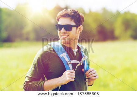 travel, hiking, backpacking, tourism and people concept - happy young man in sunglasses with backpack walking outdoors