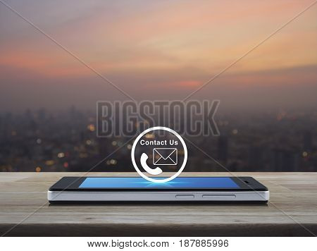 Telephone and mail icon button on modern smart phone screen on wooden table over blur of cityscape on warm light sundown Contact us concept