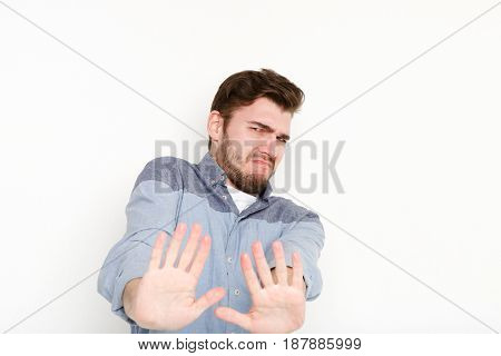 Man expressing disgust on face, grimacing on white studio background, cutout. Negative emotions