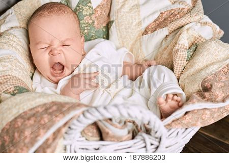 Caucasian infant yawning. Baby with mouth wide open.
