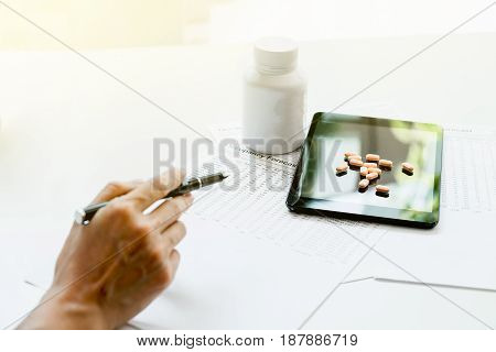 View of hand's doctor pointing to pad drug and equipment on foreground table Health care and Medical concept.