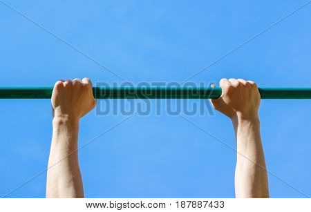 Male hands holding the horizontal bar. Close up.