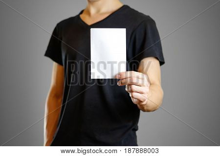 Man In A Black Shirt Holding A White Sheet Of Paper. Empty Flyer. Isolated
