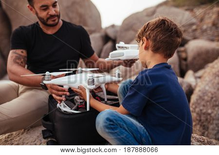 Young Man With His Son At The Beach With A Drone