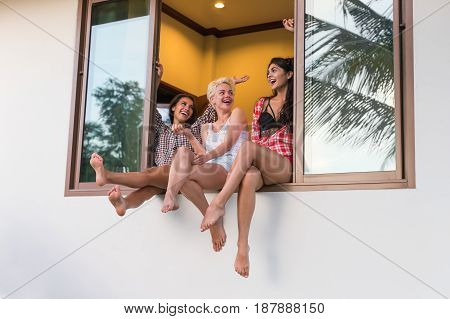 Young Girls Group Sitting On Window Sill Talking, Beautiful Woman Friends Communication Exterior View