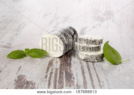 Goat cheese with basil on wooden table. Rustic vintage goat cheese background.
