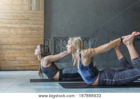 Women in yoga class, bow pose stretching. Girls do exercises. Healthy lifestyle in fitness club