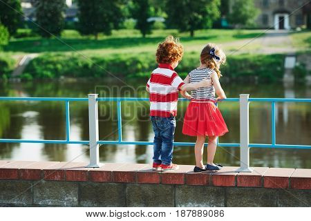 photo of cute little hugging children on the promenade