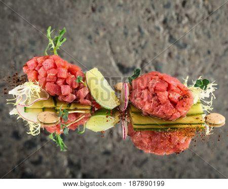 Fresh tuna tartar with garnish over concrete background