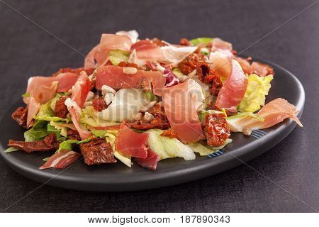 Mixes salad with dried tomatoes and ham on plate. Culinary salad eating.