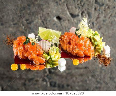 Fresh salmon tartar with garnish over concrete background