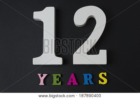 Letters And Numbers For Twelve Years On A Black Background.