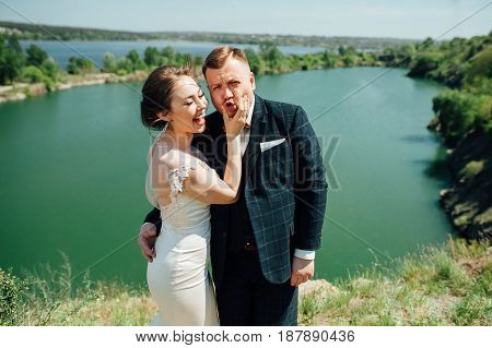 The bride and groom at a wedding Day walking outdoors on a spring nature near a lake. A newlywed couple, happy newlywed woman and man embracing in a green park.