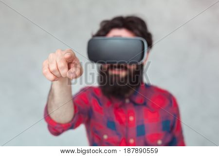 Young bearded man in VR glasses pointing at camera on grey background.