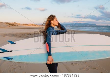 Sporty surf woman in wetsuit at sunset or sunrise on ocean