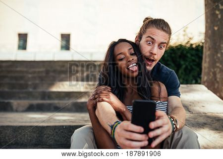 Happy couple in love making selfie together outdoors.