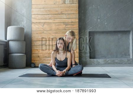 Yoga teacher and beginner in class, making asana exercises. Lotus pose. Healthy lifestyle in fitness club. Stretching with coach