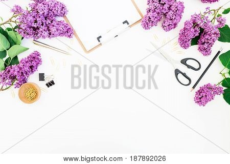 Freelance workspace with clipboard, notebook, scissors, lilac and accessories on white background. Flat lay, top view. Beauty blogger concept.