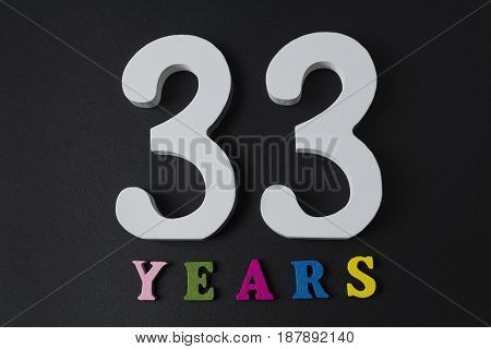 Letters And Numbers Thirty-three Years On A Black Background.